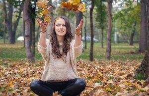 Mädchen sitzt im Laub und wirft es hoch. Sie überlegt sich dabei einen tollen Titel zu ihrer neuen Blogparade, die sie demnächst veranstalten möchte