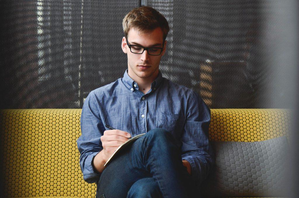 junge Mann schreibt Notizen in sein Notizbuch. Er plant seine nächste Blogparade