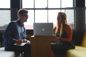Eine junge Frau zeigt einem jungen Mann am PC ihren Beitrag zur Blogparade. Er zeigt sich beeindruckt und interessiert.