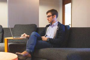 junger Mann, der am Notebook die Besucherzahlen seines Blogs überprüft. Er wird bemerken, dass sie steigen, wenn er eine Blogparade veranstaltet, oder an einer Blogparade teilnimmt