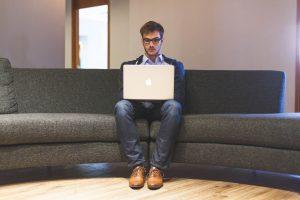 Junger Mann sitzt ratlos vor seinem Macbook. Er hat keine Idee für seinen nächsten Blogartikel. Eine Blogparade kann ihm helfen, ein passendes Thema und die fehlende Inspiration zu finden.