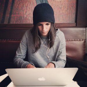Mädchen mit Mütze sitzt vor dem Macbook und verfasst einen tollen Beitrag zu einer Blogparade
